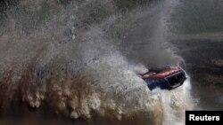 Sébastien Loeb de la France roule sur une flaque d'eau avec sa Peugeot pendant le prologue Buenos Aires-Rosario du Rallye Dakar 2016 à Arrecifes, Argentine, 2 janvier, 2016.