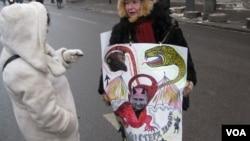 今年1月份的莫斯科反政府抗议集会中,一名女示威者手拿讽刺普京的宣传画(美国之音白桦拍摄)