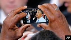 President Barack Obama is seen on a phone camera as he greets the crowd after speaking in Phoenix, Arizona, Aug. 6, 2013.