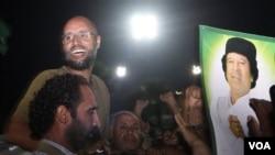Putera Moammar Gaddafi, Seif al-Islam (berkacamata) menyapa para anggota pasukan pro-Gaddafi di ibukota Tripoli (23/8). Kemunculan Seif di Tripoli sekaligus menyanggah klaim pemberontak Libya sebelumnya bahwa Seif al-Islam telah ditangkap.