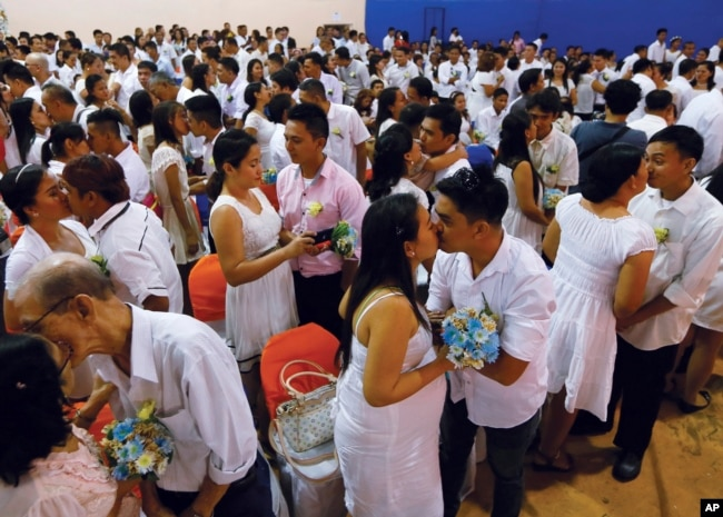 Filipino couples kiss during a mass wedding ahead of Sunday's Valentine's Day celebration in Manila, Philippines, Feb. 12, 2016 (AP Photo/Bullit Marquez)