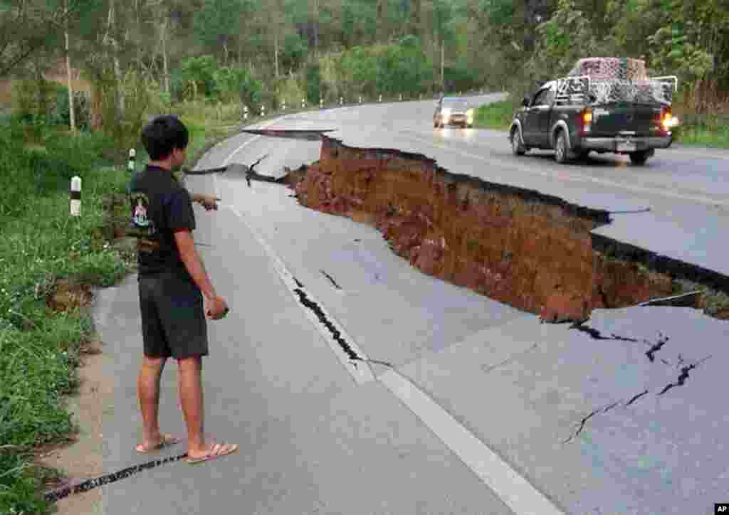 A man points at a big crack in a damaged road following a strong earthquake in the Phan district of Chiang Rai province, northern Thailand.