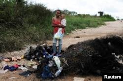 La venezolana Joanna y su hijo Bruno, del estado Anzoátegui, posan junto a sus pertenencias y colchones quemados por civiles mientras sostiene pañales donados en el control fronterizo de Pacaraima, estado de Roraima, Brasil, el 19 de agosto de 2018.