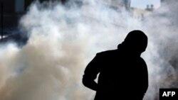 Một người biểu tình chống chính phủ Bahrain chạy tránh hơi cay do cảnh sát bắn