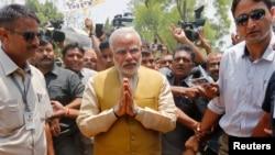 Kandidat Perdana Menteri India dari oposisi nasionalis Hindu partai Bharatiya Janata (BJP), Narendra Modi (tengah), tiba di rumah kediaman ibunya di Gandhinagar, negara bagian Gujarat, untuk meminta restu (16/5). Narendra Modi, diperkirakan kalangan luas akan menjadi perdana menteri India, menyusul kemenangan partainya dalam Pemilu 2014.