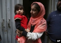 Hadiya Khalil, left, who survived a shoot-out by counter-terrorism officers, is carried by an unidentified relative at her home in Lahore, Pakistan, Jan. 20, 2019.