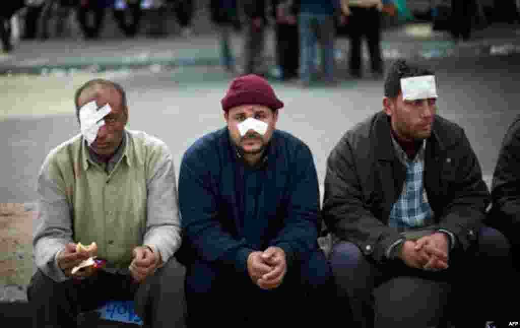 Wounded Egyptian anti government protesters sitin Cairo's main square, Egypt, Egypt, Thursday, Feb. 3, 2011. New clashes are heating up and shots are being fired in the air around Cairo's central Tahrir Square as anti-government protesters push back regi