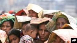 一名孟加拉国妇女在达卡一家米店排队时为怀抱中的婴儿遮挡烈日。(资料照)
