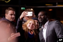 "FILE - Actor Omar Sy poses for selfies with fans before the premiere of the movie ""Inferno"" in Berlin, Oct. 10, 2016."
