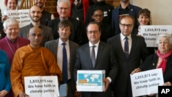France's President Francois Hollande, center, holds a box containing an international petition to support the climate talks as he poses with religious figures for a group photo at the Elysee Palace in Paris, Dec. 10, 2015.