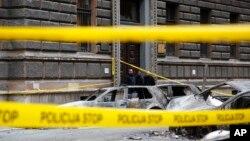 Mobil-mobil yang hangus di depan gedung pemerintah yang terbakar menyusul protes-protes di ibukota Sarajevo, Bosnia (8/2). (AP/Amel Emric)