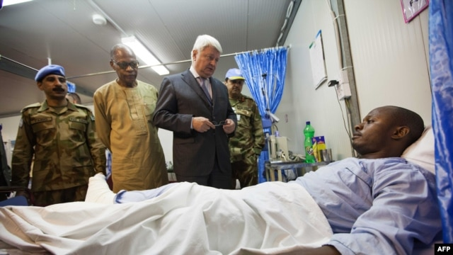 A handout picture released by the United Nations-African Union Mission in Darfur (UNAMID) shows Hervé Ladsous, the United Nations Under-Secretary-General for Peacekeeping Operations, meing in the UNAMID base in Nyala, South Darfur, one of the three injured UNAMID peacekeepers attacked in an ambush near Labado, East Darfur, on July 4, 2013.