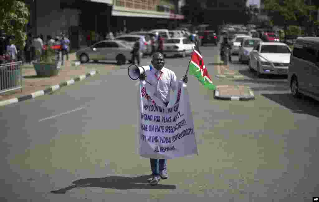 A protester shouts into a megaphone while holding the Kenyan flag outside the Parliament building in Nairobi, Kenya Thursday, Dec. 18, 2014.
