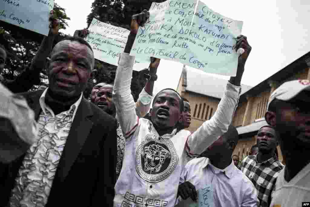 Des Congolais brandissent des pancartes lors d'une manifestation après un service catholique pour commémorer les victimes de la répression de la marche du mois dernier à l'extérieur d'une cathédrale à Kinshasa, le 12 janvier 2018.