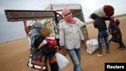 Người Kurd từ thị trấn Kobani ở Syria tải đồ đạc lên xe tải gần biên giới Thổ Nhĩ Kỳ-Syria. Giao tranh tại Kobani đã buộc 200.000 người chạy lánh nạn tới khu vực đông nam của Thổ Nhĩ Kỳ.