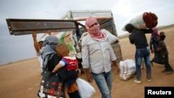 叙利亚库尔德难民在叙利亚-土耳其边界把东西放到车上