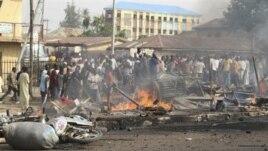 Mutane sun taru a wani wurin da bam ya tashi kan wata hanya a Kaduna, arewacin Najeriya ran 8 Afrilu, 2012.