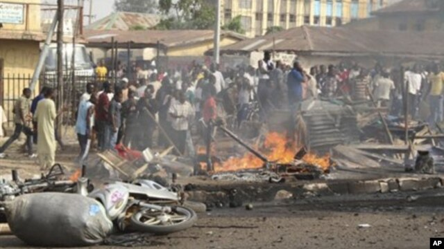 People gather at the site of a bomb explosion at a road in Kaduna, Nigeria on Sunday, April 8, 2012.