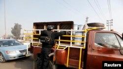 Cảnh sát kiểm tra chiếc xe hơi tại một chốt kiểm soát. An ninh được tăng cường sau vụ tấn công bằng bom tại quận Abu Ghraib ở hướng tây Baghdad, 9/1/14