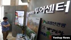 개성공단 회담 타결로 금강산 관광 재개에 대한 기대감도 높아지고 있는 가운데, 16일 오전 서울 현대아산 로비에 위치한 투어센터에서 한 직원이 홍보물을 점검하고 있다.