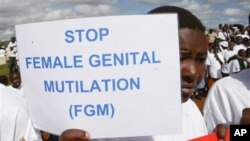 FILE - A Masai girl holds protest sign during an anti-Female Genital Mutilation (FGM) run in Kilgoris, Kenya.