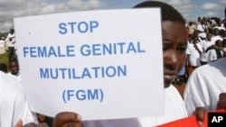 FILE - Masai girl holds protest sign during anti-Female Genital Mutilation run in Kilgoris, Kenya. The practice is found in Singapore, and according to the U.N. in 30 other countries as well, almost all in Africa. Indonesia is the only Asian country the U.N. cites.