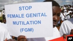 Masai girl holds protest sign during anti-Female Genital Mutilation (FGM) run in Kilgoris, Kenya.