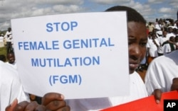FILE - Masai girl holds protest sign during anti-Female Genital Mutilation (FGM) run in Kilgoris, Kenya