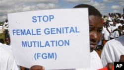 FILE - Masai girl holds protest sign during anti-Female Genital Mutilation (FGM) run in Kilgoris, Kenya.