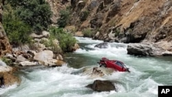This Aug. 5, 2017, photo provided by the Fresno County Sheriff's office shows a car in the middle of Kings River near Fresno, Calif.