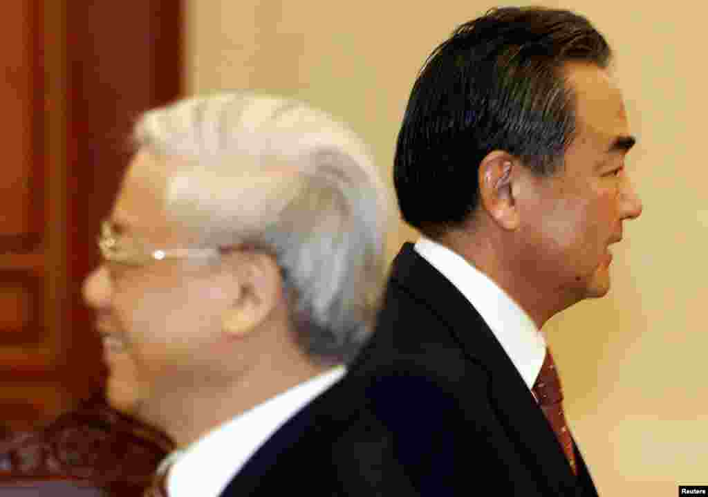 China's Foreign Minister Wang Yi (R) walks past Vietnam's Communist Party's General Secretary Nguyen Phu Trong upon his arrival for the meeting at the party's head office in Hanoi, Vietnam.
