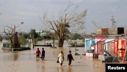 열대성 폭풍 파일린이 강타한 인도 동부 오디사주에서 주민들이 물에 잠긴 거리를 건너고 있다.