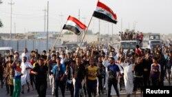 伊拉克志願者加入軍隊與激進分子作戰﹐他們手持武器和伊拉克國旗在巴格達東部遊行