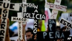 """Demonstran membawa salib bertuliskan """"Polisi Narkoba"""" dalam protes yang menuntut ditemukannya 43 mahasiswa yang diculik, di Guerrero, Mexico City (5/11). (AP/Eduardo Verdugo)"""