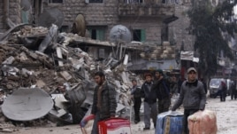 Residents evacuate their houses after being targeted by missiles fired by forces loyal to Syria's President Bashar al-Assad, in Aleppo's al-Mashhad district, Syria, January 9, 2013.