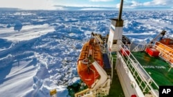 In this image provided by Australasian Antarctic Expedition/Footloose Fotography, Russian ship Akademik Shokalskiy is shown trapped in thick Antarctic ice, 1,500 nautical miles south of Hobart, Australia, Friday, Dec. 27, 2013.