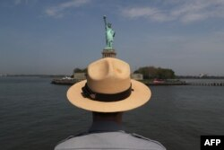 FILE - A U.S. park ranger looks towards the Statue of Liberty while in route to Ellis Island.