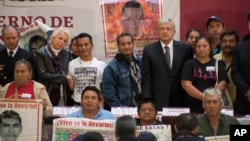 Mexico's President Andres Manuel Lopez Obrador poses for a photo with the parents of the 43 missing Mexican students of Ayotzinapa, at the National Palace in Mexico City, Monday, Dec. 3, 2018. (AP Photo/Christian Palma)