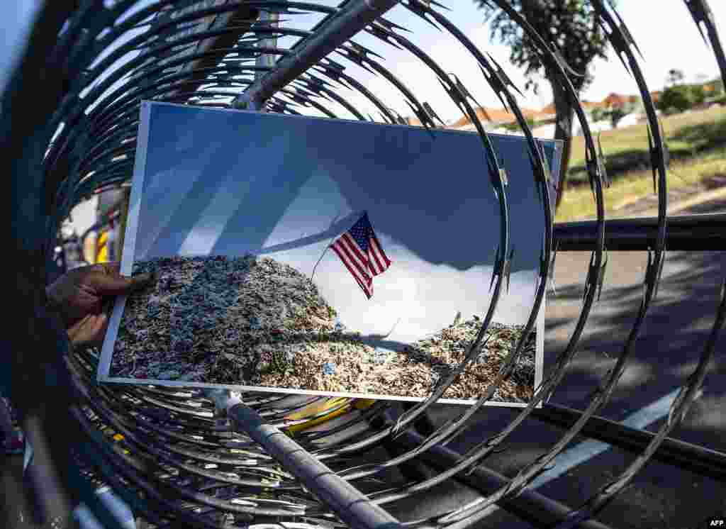 An Indonesian protester displays a picture showing the US flag on top of a trash dump during a rally in front of US consulate general office in Surabaya, in East Java, demanding the US to stop exporting waste to Indonesia.