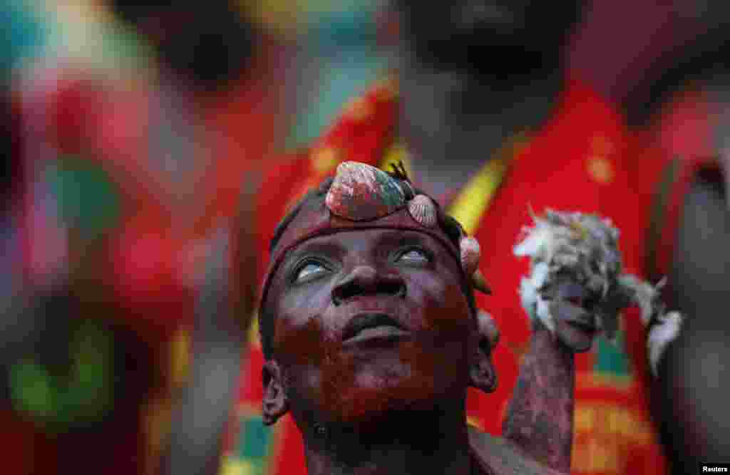 A Burkina Faso fan prays before the Group A soccer match against Equatorial Guinea at the 2015 African Cup of Nations in Bata, Equatorial Guinea.