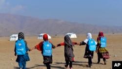 Афганские школьницы направляются в свои учебные классы, расположенные в палатках в окрестностях Джелалабада.