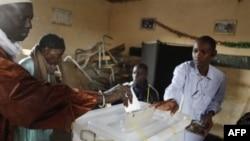 Nhân viên bầu cử giúp cử tri bỏ phiếu tại một phòng phiếu trong khu phố Cambarene của Dakar, Senegal, ngày 26/2/2012