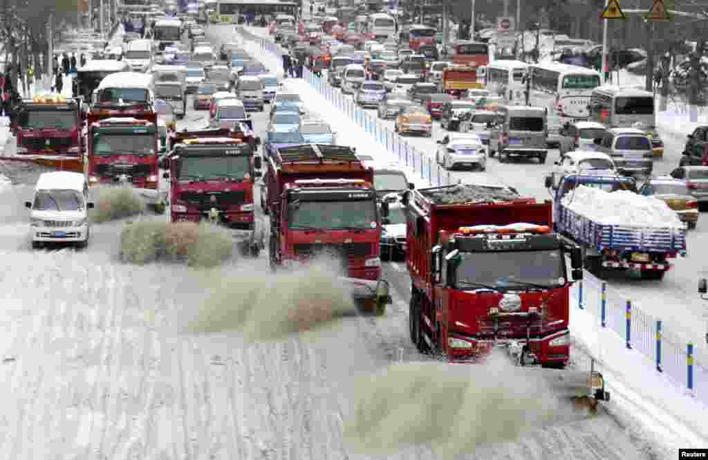 Snow clearing vehicles work on a road in Harbin, Heilongjiang province, China.