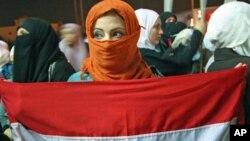 A woman holds a Syrian flag as Jordanians and Syrians protest against Syrian President Bashar Al-Assad in Amman, Jordan, October 3, 2011.