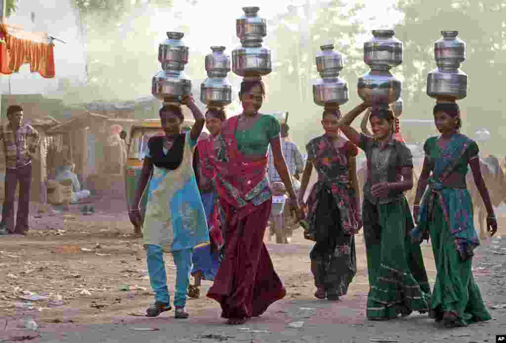 Indian village girls carry water in pitchers on their heads at Juval village, about 40 kilometers from Ahmadabad, India. Water scarcity in the scorching summer is a common sight in villages in India.