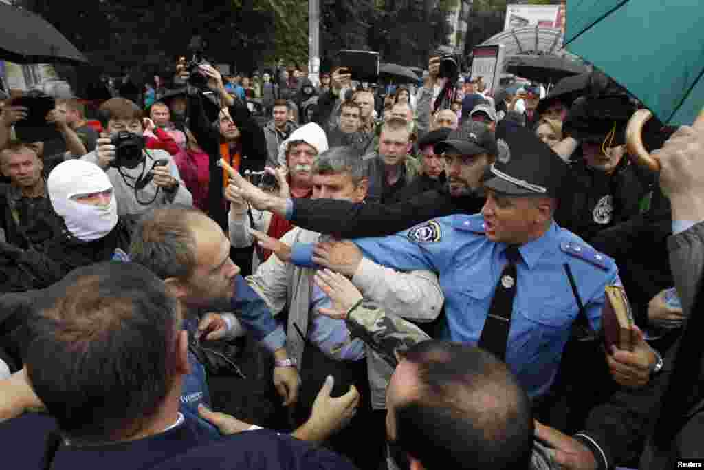 A police officer tries to prevent activists and relatives of Ukraine soldiers from getting into the defencse ministry building during a protest, in Kyiv, Aug. 28, 2014.