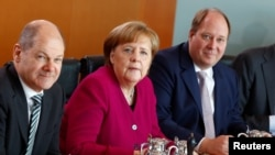German Finance Minister and vice-chancellor Olaf Scholz, Chancellor Angela Merkel and Chancellery's Chief of Staff Helge Braun before the weekly cabinet meeting in Berlin, Germany, March 21, 2018.