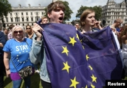 People hold flags during a 'March for Europe' demonstration against Britain's decision to leave the European Union, in central London, Britain, July 2, 2016.