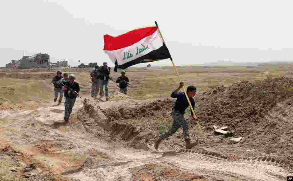 A member of the Iraqi security forces runs to plant the national flag during clashes to regain Tikrit from Islamic State militants.
