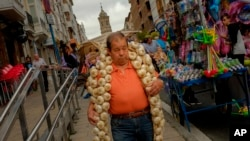 A man carries a strip of garlic during the garlic fair in Vitoria, northern Spain, July 2016. (AP Photo/Alvaro Barrientos)
